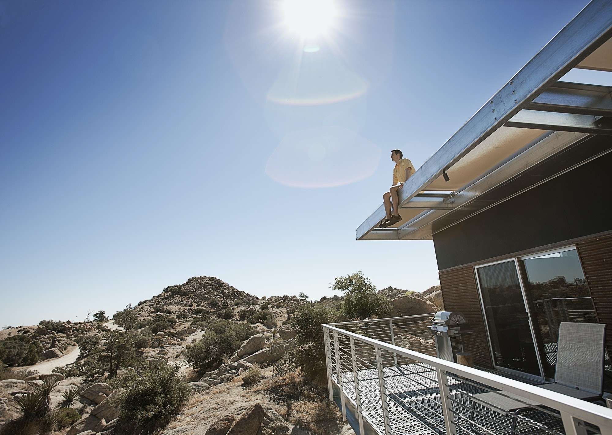 A man sitting on the roof overhang of an eco home in the desert landscape.
