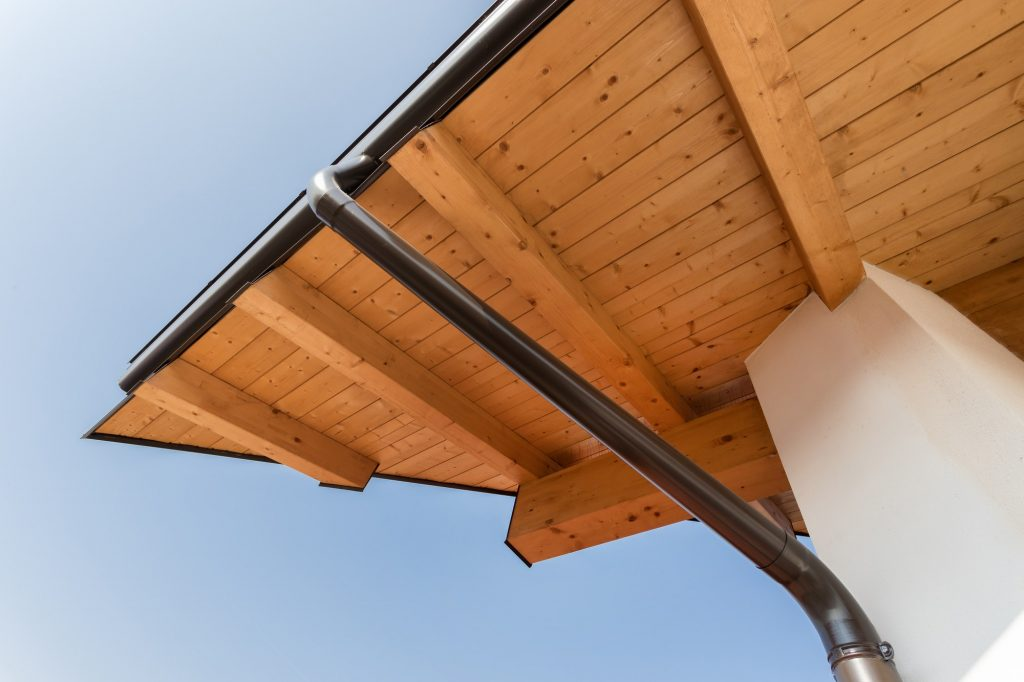 New wooden warm ecological house roof with steel gutter rain system