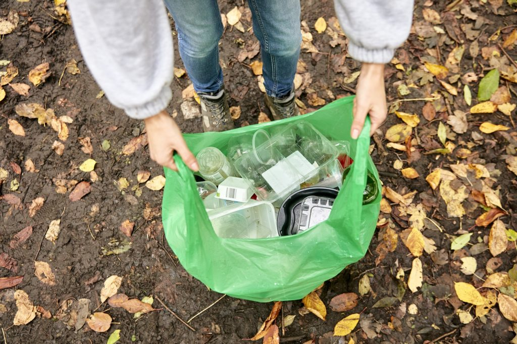 Plastic bag being held open filled with plastic litter