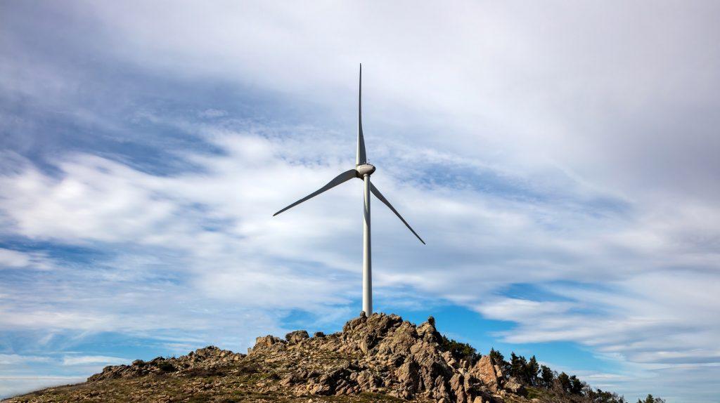 Wind turbine, renewable energy on a rocky hill.