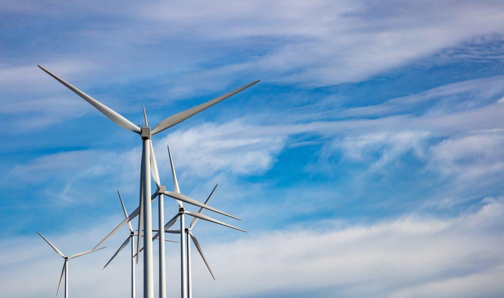 Wind turbines, renewable energy on blue cloudy sky background. Wind farm